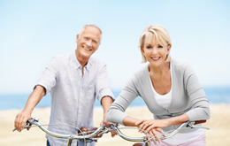 retired couple riding bikes on the beach enjoying life