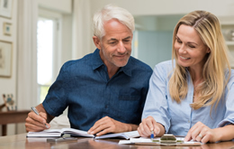 Retired couple sitting at home going through their finances and investment management services